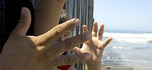 child hand, adult hand, fence, ocean