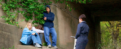 woman speaking with young people under a bridge